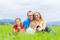 Familia feliz al aire libre que se sienta en hierba Imágenes de archivo libres de regalías