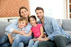 Familia feliz alegre que se sienta en casa Fotografía de archivo