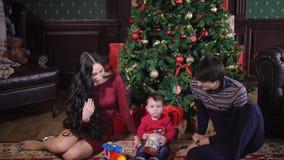 Familia feliz bien vestida que se sienta en la manta cerca del árbol de navidad en una sala de estar caliente de la casa La mamá  metrajes