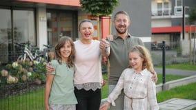 Familia feliz cerca de su nueva casa Concepto 6 de las propiedades inmobiliarias Se divierten mucho junto almacen de metraje de vídeo