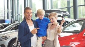 Familia feliz cerca del nuevo coche Centro de la representación auto almacen de metraje de vídeo