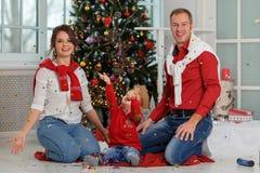 Familia feliz con confeti en el fondo del árbol de navidad con los regalos Imagen de archivo