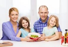 Familia feliz con dos niños con la ensalada en casa foto de archivo libre de regalías