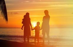 Familia feliz con dos niños en la playa de la puesta del sol Fotografía de archivo