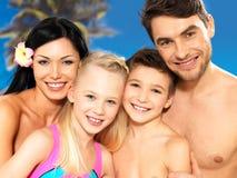Familia feliz con dos niños en la playa tropical Foto de archivo