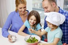 Familia feliz con dos niños que cocinan en casa imagen de archivo