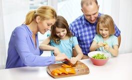 Familia feliz con dos niños que cocinan en casa fotos de archivo
