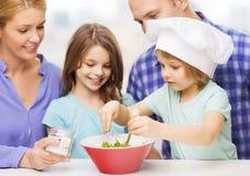 Familia feliz con dos niños que comen en casa Foto de archivo