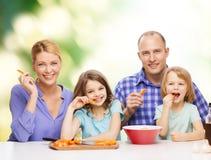 Familia feliz con dos niños que comen en casa Fotografía de archivo libre de regalías