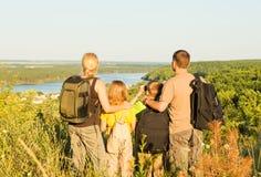 Familia feliz con dos niños que se colocan en la colina y la mirada Imagen de archivo libre de regalías