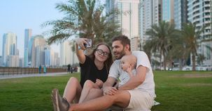 Familia feliz con dos ni?os que se sientan junto en hierba en parque y que toman un selfie Con smartphone metrajes