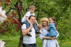 Familia feliz con dos niños en jardín Imagen de archivo