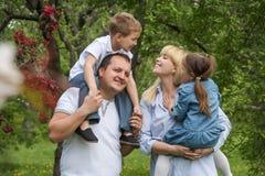 Familia feliz con dos niños que se divierten en jardín Imagen de archivo libre de regalías
