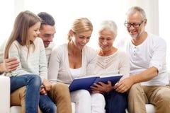 Familia feliz con el álbum del libro o de foto en casa Imagen de archivo libre de regalías