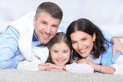 Familia feliz con el abarcamiento de la mentira de la hija Imagen de archivo libre de regalías