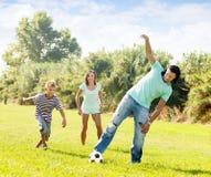 Familia feliz con el adolescente que juega en fútbol Imagenes de archivo