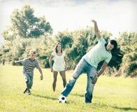 Familia feliz con el adolescente que juega en fútbol Foto de archivo libre de regalías