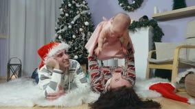 Familia feliz con el bebé debajo del árbol de navidad metrajes