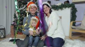 Familia feliz con el bebé en sombreros del ` s de Papá Noel almacen de video