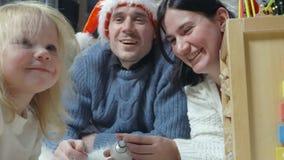 Familia feliz con el bebé en sombreros del ` s de Papá Noel almacen de metraje de vídeo