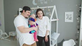 Familia feliz con el bebé que mira hacia fuera la ventana en casa almacen de metraje de vídeo