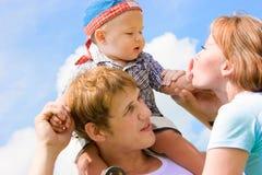 Familia feliz con el bebé sobre el cielo azul Imagenes de archivo