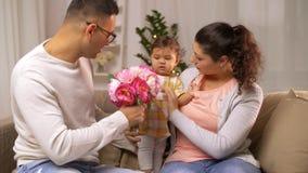 Familia feliz con el bebé y las flores en casa metrajes