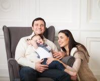 Familia feliz con el bebé de un año interior Imágenes de archivo libres de regalías
