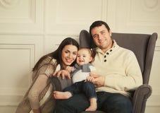 Familia feliz con el bebé de un año interior Foto de archivo