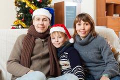 Familia feliz con el hijo en casa con el árbol de navidad Foto de archivo