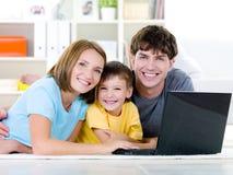 Familia feliz con el hijo en el país con la computadora portátil Imágenes de archivo libres de regalías