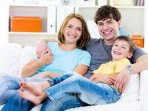 Familia feliz con el hijo en el sofá Foto de archivo