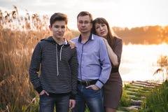 Familia feliz con el hijo que presenta en un fondo de una puesta del sol en el río Fotografía de archivo libre de regalías