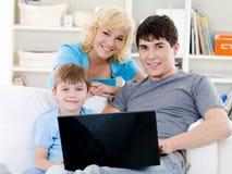 Familia feliz con el hijo y la computadora portátil en el país Imagen de archivo