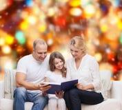 Familia feliz con el libro en casa Fotografía de archivo