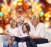 Familia feliz con el libro en casa Fotos de archivo libres de regalías