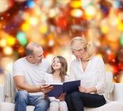 Familia feliz con el libro en casa Imagen de archivo libre de regalías