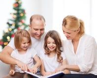 Familia feliz con el libro en casa Imágenes de archivo libres de regalías