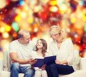 Familia feliz con el libro en casa Foto de archivo libre de regalías