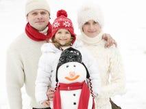 Familia feliz con el muñeco de nieve Fotografía de archivo