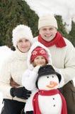 Familia feliz con el muñeco de nieve Foto de archivo libre de regalías