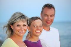 Familia feliz con el muchacho sonriente en la playa por la tarde Fotos de archivo