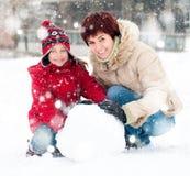 Familia feliz con el muñeco de nieve Fotos de archivo libres de regalías