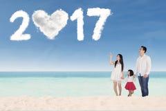 Familia feliz con el número 2017 en la playa Fotografía de archivo