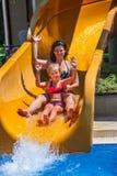 Familia feliz con el niño en el tobogán acuático en el aquapark Fotos de archivo libres de regalías