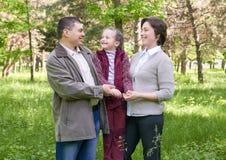 Familia feliz con el niño en parque del verano, luz del sol, hierba verde y árboles Imagenes de archivo