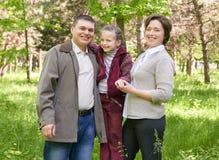 Familia feliz con el niño en parque del verano, luz del sol, hierba verde y árboles Imagen de archivo libre de regalías