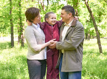 Familia feliz con el niño en parque del verano, luz del sol, hierba verde y árboles Foto de archivo