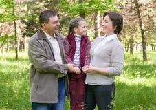Familia feliz con el niño en parque del verano, luz del sol, hierba verde y árboles Fotos de archivo libres de regalías