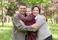 Familia feliz con el niño en parque del verano, luz del sol, hierba verde y árboles Fotografía de archivo